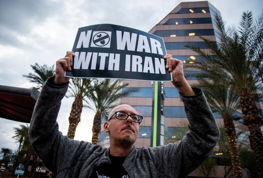 Jeffery Fetterhoff protests the Trump administration's killing of a top Iranian general and decision to send 3,000 more soldiers to the Middle East on the corner of Camelback and 24th Street in Phoenix on Thursday, Jan. 9, 2020.