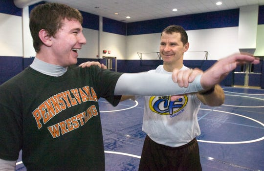 Dallastown wrestling coach Dave Gable jokes around while he stretches out his son Clay's shoulder before a practice leading up to the PIAA championships in 2009. Clay would go on to win the state title at 171 pounds and then compete at the Air Force Academy.