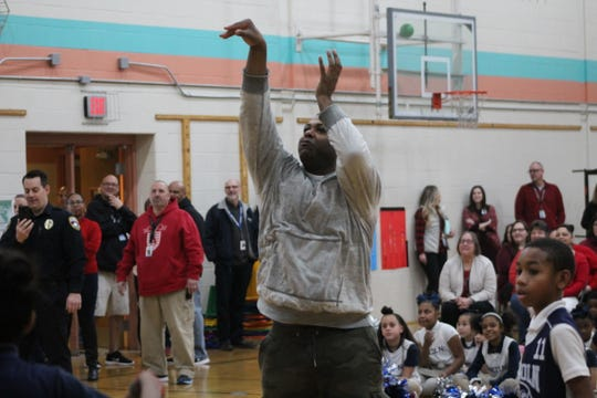 Police Commissioner Osborne Robinson III takes a shot during the free throw competition at Lincoln Charter School.