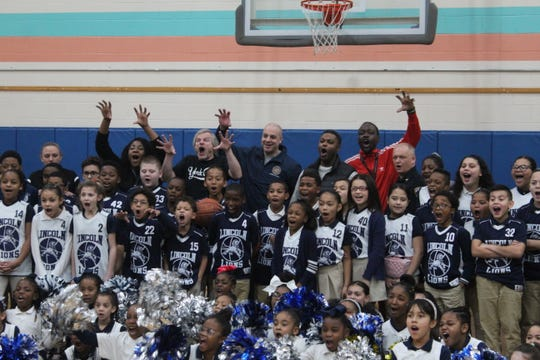 The participants from the free throw competition taking a picture with students and staff from Lincoln Charter School