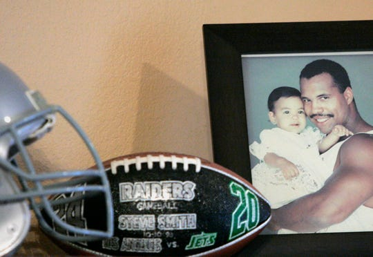 A photo of former Penn State and Oakland Raider star Steve Smith with his daughter Jazmin with an Oakland Raider's game ball and helmet from 2006. (AP Photo/Tony Gutierrez)