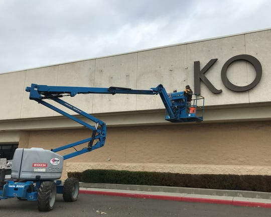 Workers with Tri-Shasta Construction take down the Shopko sign in front of the shuttered department store on Friday, Jan. 10, 2020.