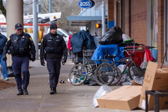 Police patrol the area as sanitation crews clean up sidewalks in downtown Salem for the second day, on Jan. 10, 2020.