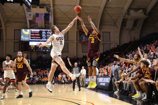 Arizona State's Rob Edwards, center right, shoots a 3-pointer over Oregon State's Zach Reichle during the second half of an NCAA college basketball game in Corvallis, Ore., Thursday, Jan. 9, 2020.