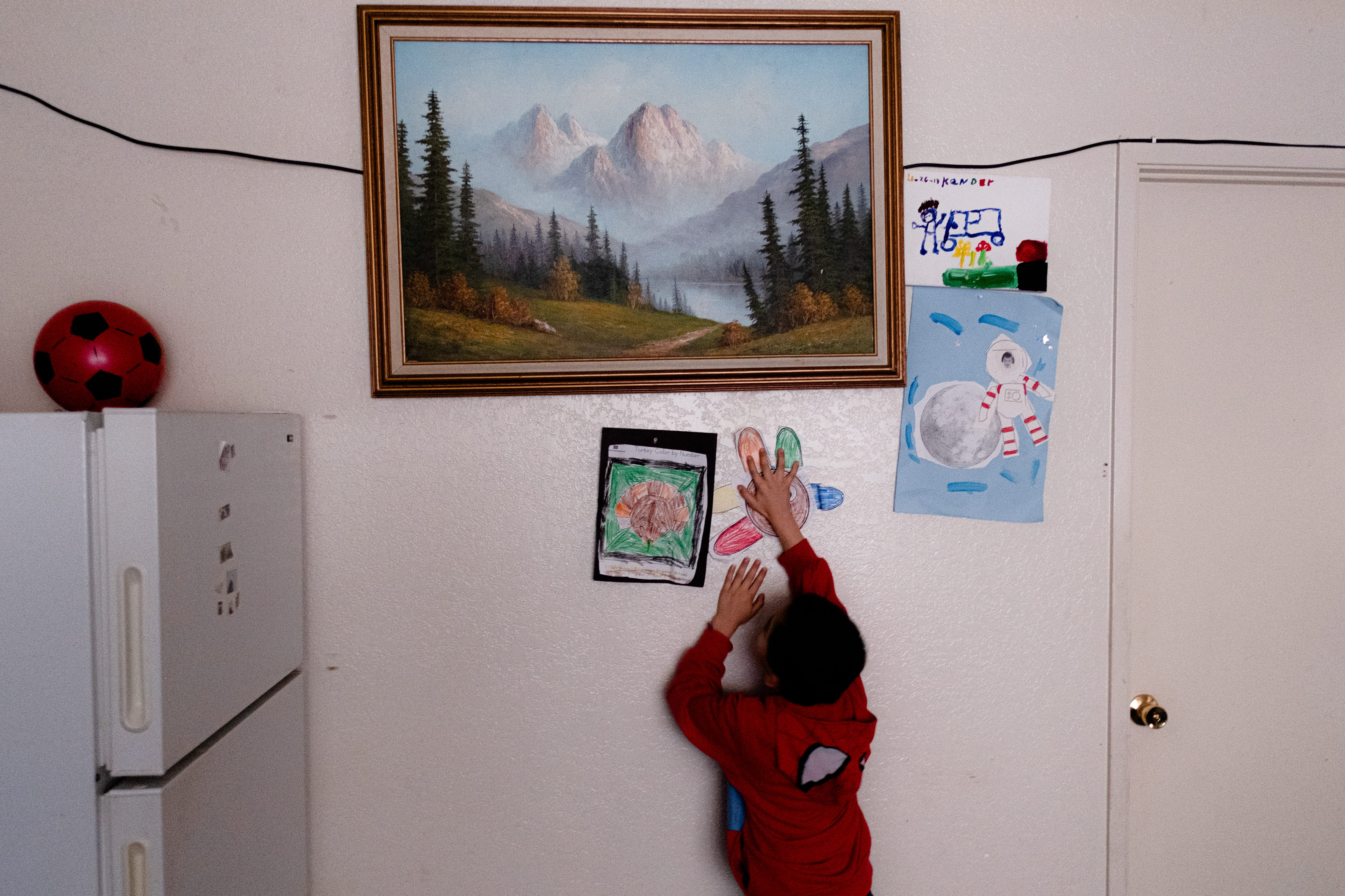 """Kender Ricardez Tobon, 5, stamps a drawing he made at school on the walls of his home. He lives in a small apartment complex on the East Side of Salinas with his grandmother Eufemia """"Jenni"""" Aguilar."""