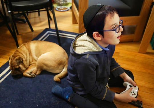In this Dec. 30, 2019, photo, Gavriel Menachem Blum, 10, plays a video game before Shabbat dinner at his family's home in New York. Like many Jews who observe Sabbath, Blum refrains from playing video games and using other electronics after sundown.