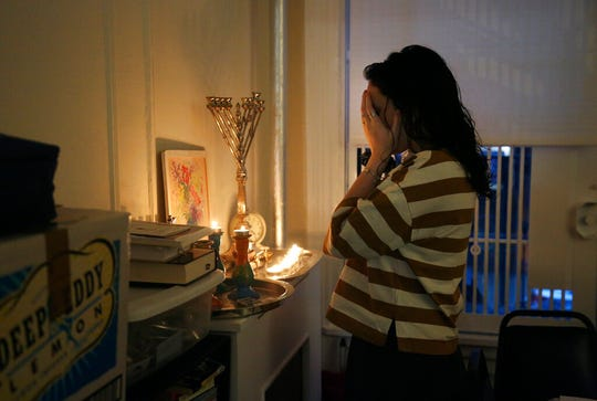 """In this Friday, Jan. 3, 2020, photo, Chana Blum, 14, recites a blessing after lighting candles for Shabbat dinner in her family's home in New York. Two days later, Blum joined her older sister at the """"No Hate, No Fear"""" solidarity march organized by New York's Jewish community in response to the recent string in anti-Semitic attacks."""