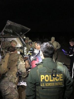 Several law enforcement agencies provide first aid to a man who they believe was shot during a shootout between Mexican police and the Mexican cartel.