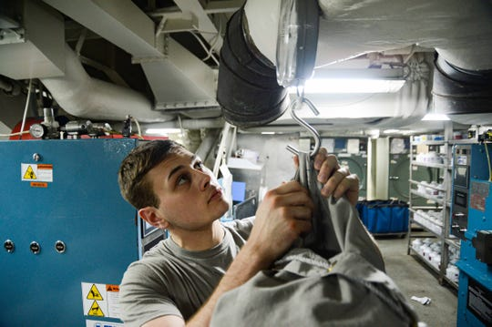 Air Traffic Controlman Airman Adam Hartman, from San Angelo, Texas, weighs a bag of laundry in ship's laundry aboard the aircraft carrier USS Harry S. Truman in the Arabian Sea Jan. 5, 2020.