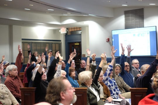 Sussex County residents raise their hands to oppose an application to build 227 homes in an environmentally sensitive area that contains wetlands and forest. Thursday, Jan. 9 2019.