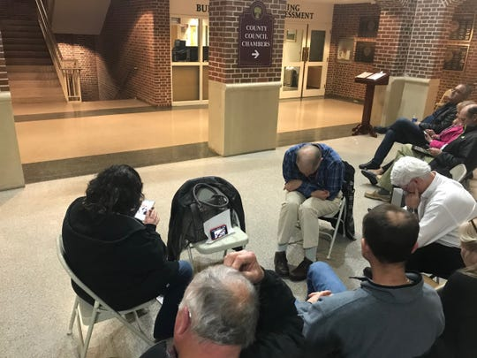 Several Sussex County residents waited hours to enter a planning and zoning meeting in Georgetown Thursday night. Some huddled around a mobile phone to watch a live broadcast because the building's recording was inaudible. Thursday, Jan. 9, 2019.