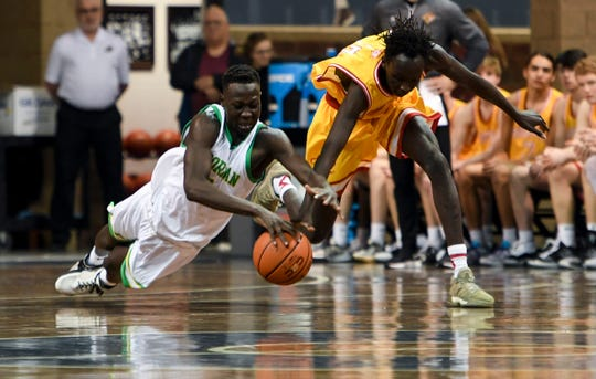 O'Gorman's Akoi Akoi (3) and Roosevelt's Koor Kuol (13) dive for a loose ball during the Throwback Classic game on Thursday, Jan. 9, 2020 at the Sanford Pentagon.