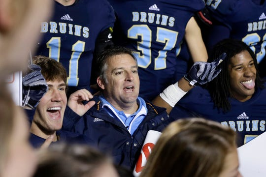 Pulaski Academy coach Kevin Kelley, center, celebrates with his team after the Arkansas Class 5A High School Championship football game in Little Rock, Ark., Saturday, Dec. 6, 2014. Pulaski Academy defeated Wynne High School 38-28.