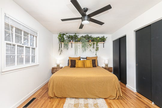 The master bedroom features an abundance of plants cascading from a high shelf. Austin says the plant farthest left is a rat-tail cactus, the first plant his grandmother gave him.