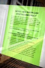 A sign announcing changes in federal law is posted Friday, Jan. 10, 2020, at a St. Cloud Kwik Trip store.