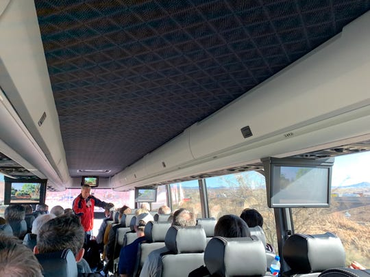 Washington City Mayor Ken Neilson talks about the history of the town as the tour bus drives by new developments in the city.