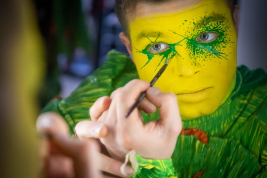 Kilian Mongey, one of Cirque du Soleil's OVO tumblers, paints his face with makeup before a performance.