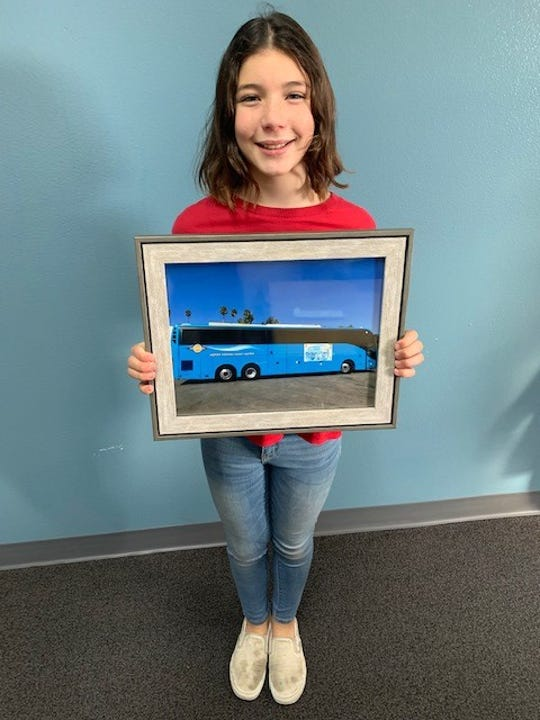 Leila Martinez, 11, holding photo of her winning drawing displayed on the side of a Ventura County Transportation Commission bus.