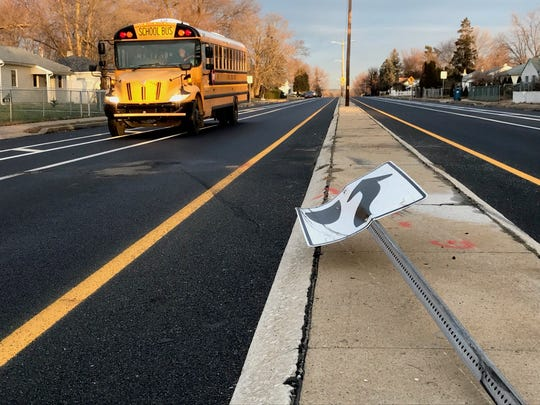 A school bus drives past a downed road sign at the scene of a fatal crash Thursday that left a teen driver dead.