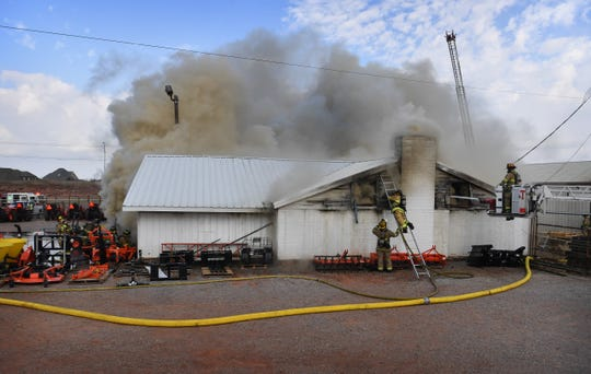 Heavy smoke billows across Seymour Highway Friday morning as firefighters work to control a three-alarm fire at Berend Turf & Tractor.