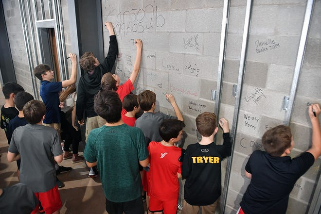 Dozens for junior high and high school students sign their names on the inside wall of the new Blended Learning Center under construction at Christ Academy Friday.