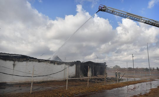 One of two aerial trucks sprays water Friday morning as the Wichita Falls Fire Department worked a three-alarm fire at Berend Turf & Tractor on Seymour Highway.