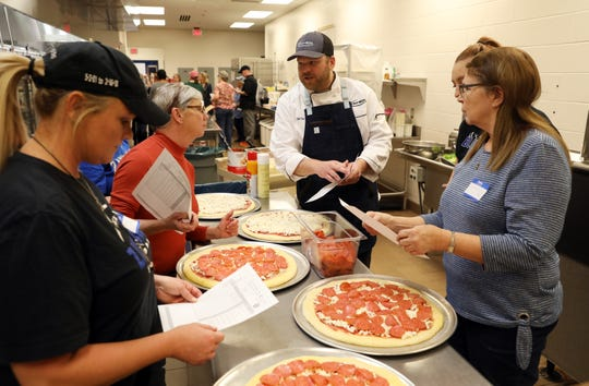 Chef Cory Freeman, with Taher, a food services management company, talks about making fresh pizza with a group of cafeteria personnel during a training session at Zanesville High School recently. The district is increasing the amount of freshly made foods at their schools.