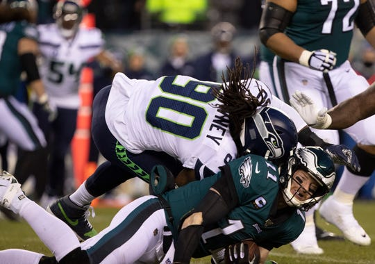 Eagles quarterback Carson Wentz is hit by Seattle Seahawks defensive end Jadeveon Clowney during the first quarter in a NFC Wild Card playoff football game.