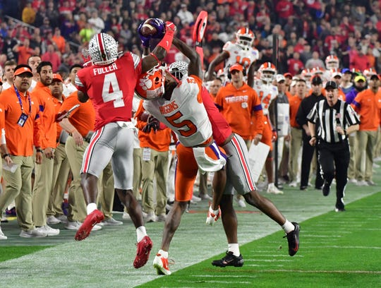 Clemson wide receiver Tee Higgins (5) tries to catch a pass between Ohio State defenders  Jordan Fuller (4) and Jeff Okudah during the 2019 Fiesta Bowl.