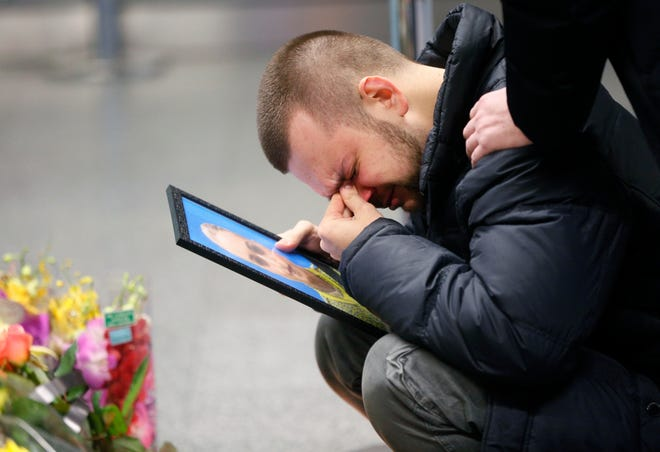 The partner of Julia Sologub, a member of the flight crew of the Ukrainian 737-800 plane that crashed on the outskirts of Tehran, reacts as he holds a portrait of her at a Jan. 10 memorial inside Borispil international airport outside in Kyiv, Ukraine.