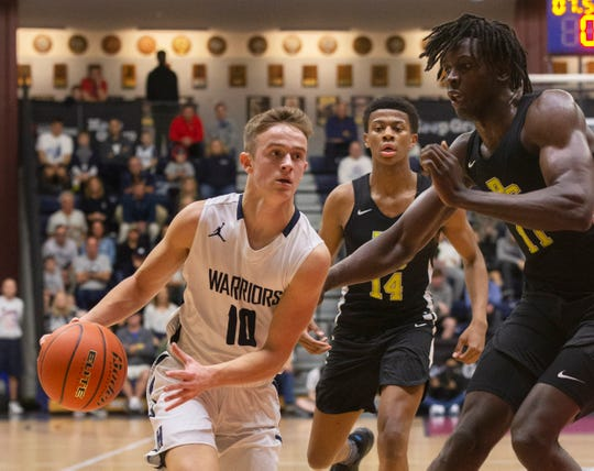 Manasquan  Ben Roy drive to the basket against Roselle Catholic Cliff Omoyuri. Manasquan Boys Basketball vs Roselle Catholic in Boardwalk Showcase in Middletown on January 11, 2020.