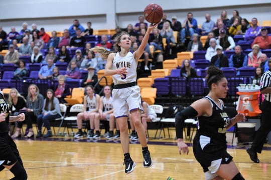 Wylie's Morgan Travis (5) lays the ball in against No. 12 Wichita Falls Rider at Bulldog Gym on Friday. Travis scored a team-high nine points, but the Lady Raiders took the District 4-5A opener 48-30.