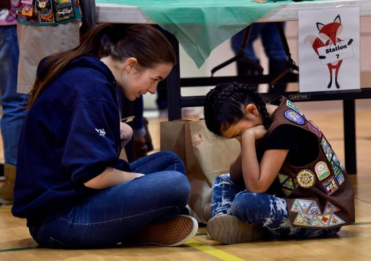 Hannah VanCamp, 17, tries to lift the spirits of Arionna Munoz, 8, about approaching people to sell them Girl Scout cookies on Saturday. Cookie University teaches girls the tools for learning confidence selling cookies and speaking with unfamiliar people to do so.