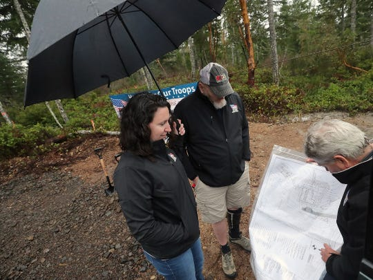 Air Force Staff Sgt. Keith Sekora and his wife Andy look over the house plans with Carey Miller, of Miller Construction, on Friday. Sekora's new home will accommodate a wheelchair and have other customizations to make life with his disability easier.