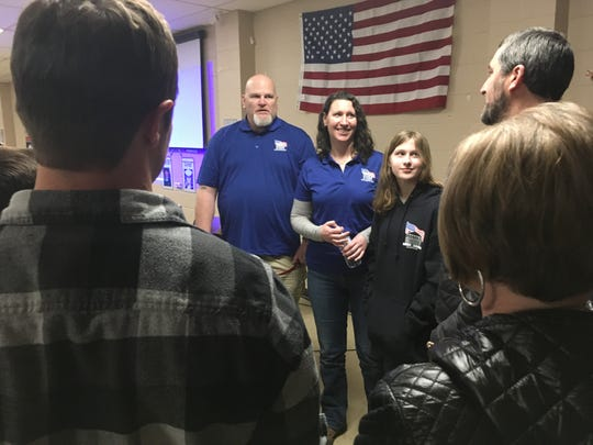 U.S. Air Force Staff Sgt. Keith Sekora with his wife, Andy, and daughter Olivia Hassler, 12, are surrounded by well-wishers at the Port Orchard Eagles hall on Saturday. Sekora of Lake Stevens, wounded in 2010 in Afghanistan, will receive a custom-built home in South Kitsap from Homes For Our Troops.
