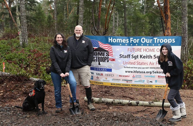 Air Force Staff Sgt. Keith Sekora, his wife Andy and stepdaughter Olivia Hassler, 12, at the site of their new home in South Kitsap on Friday, Jan. 10, 2020. Sekora, who served in Afghanistan following the Sept. 11, 2001, terrorist attacks, was disabled. The nonprofit Homes For Our Troops is building him a custom home in South Kitsap.