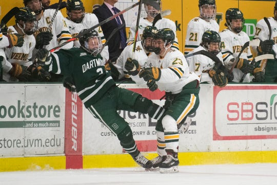 Vermont's Max Kaufman (23) checks Dartmouth's Joey Matthews (3) into the bench during the men's hockey game between the Dartmouth Big Green and the Vermont Catamounts at Gutterson Field House on Friday night January 10, 2020 in Burlington, Vermont.