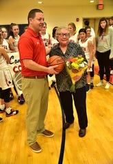 Talawanda athletic director Wes Cole presents coach Mary Jo Huismann the game ball as she collects win No. 700 in her coaching career, Jan. 11, 2020.