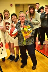 "Talawanda coach Mary Jo Huismann receives flowers and a signed ""700"" basketball upon claiming her 700th career victory as a coach, Jan. 11, 2020."
