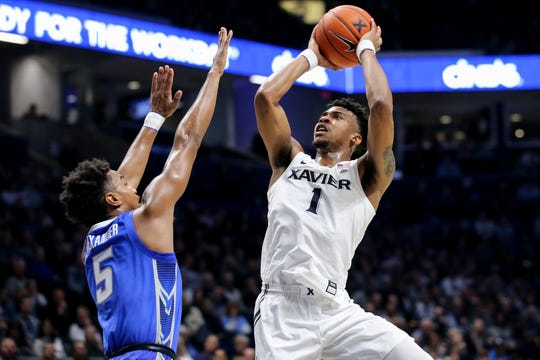 Xavier Musketeers guard Paul Scruggs (1) rises for a shot as Creighton Bluejays guard Ty-Shon Alexander (5) defends during the first half of an NCAA men's basketball game, Saturday, Jan. 11, 2020, at Cintas Center in Cincinnati.