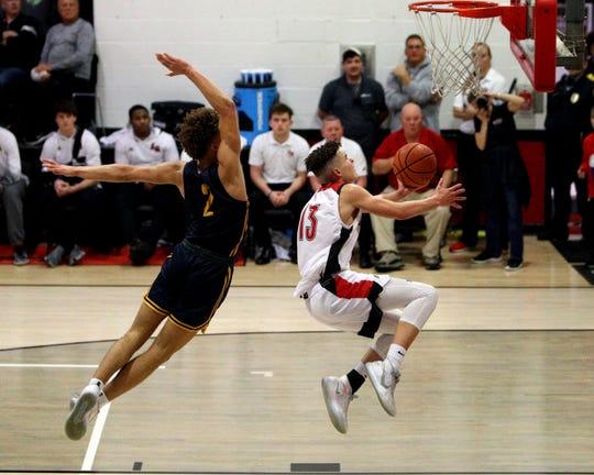La Salle guard Derek Eddings drives the lane with Moeller guard Max Land trailing the play in the boys basketball game between Moeller and La Salle High School Jan. 10, 2020. Moeller defeated La Salle 45-43.