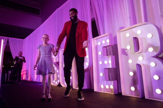 Detroit Pistons player Andre Drummond holds hand with Ava Jabczenski on stage during the Runway of Hopes and Dreams at the Detroit Pistons Performance Center in Detroit, Friday, Jan. 10, 2020.