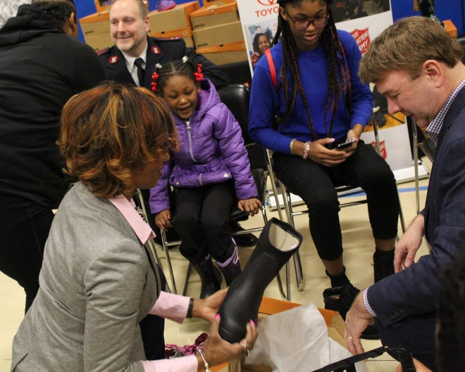 Jaylah Hambrick Daniel, 4, becomes excited as she and her sister, Joey, 14, receive new boots.
