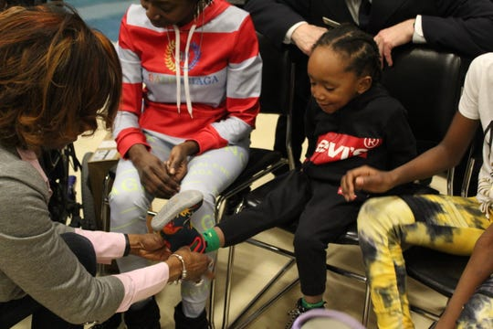 Toyota employee Kia McWhorter removes 3-year-old Charles Brown's shoes.