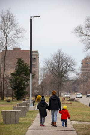 Shimekia Nichols, deputy director of Soulardarity, walks with her two children on Jan. 3, 2020 past a solar streetlight that her organization funded in Highland Park, Michigan, where DTE removed most streetlights in 2011.