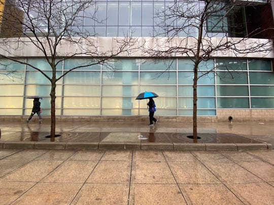 With umbrellas in hand, people make their way down Broadway Street in front of the Boll Family Y in downtown Detroit on Saturday, Jan. 11, 2020.