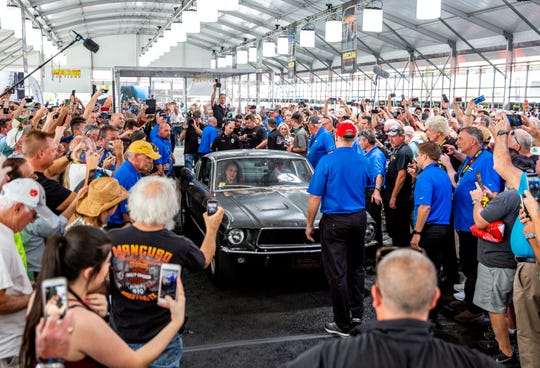 """A crowd surrounds the 1968 """"Bullitt"""" Mustang GT at auction Friday."""