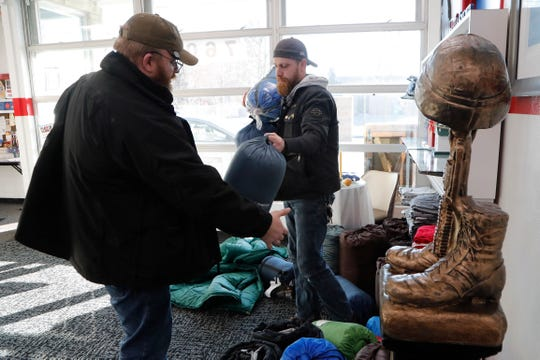 Larry Mortimer, left, helps Tim Fitzgerald load sleeping bags for the homeless Wednesday, Jan. 8, 2020, at the Bedford Township Veterans Center in Temperance, Mich.