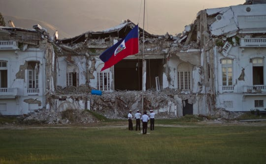 Haitian police lower the national flag in front of the damaged presidential palace on the first anniversary of the magnitude-7.0 earthquake, in Port-au-Prince, Haiti, Wednesday Jan. 12, 2011.
