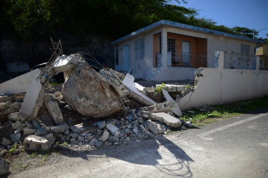 A big rock sits amid the rubble of the low wall it destroyed when it rolled down from a nearby cliff during a magnitude 5.9 earthquake in Guanica, Puerto Rico, Saturday, Jan. 11, 2020.